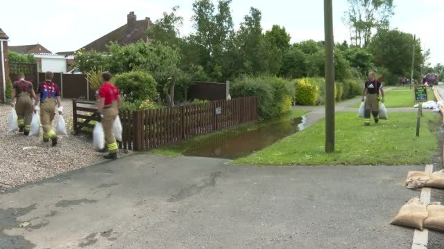 Severe flooding forces evacuation in Wainfleet Lincolnshire ENGLAND Lincolnshire Wainfleet EXT Firefighters carrying sandbags to house for flood...