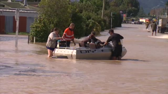 Severe flooding in town of Edgecumbe with people evacuating with belongings and dogs in boat and carrying cat in cage through submerged street
