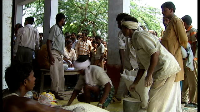 shots of local people coping in uttar pradesh sack of grain being poured onto ground and checked various shots of grain being handed out by aid... - uttar pradesh stock videos and b-roll footage