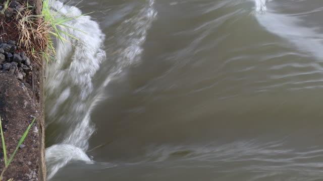 Severe flooding streams flowing underneath a concrete bridge.
