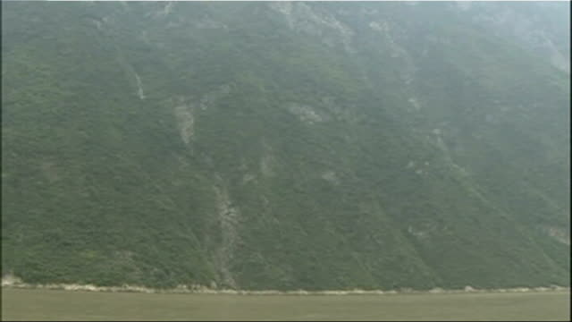 Yangtze River and wooded banks Large town on banks of Yangtze River Hubei Province Yichang Three Gorges Dam