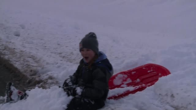 Severe gales and snow batter Britain and continental Europe Children sledging down hill Vox pops