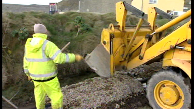 vídeos y material grabado en eventos de stock de severe gales and torrential rain predicted wales pembrokeshire man raking pebbles jcb tipping pebbles and stones onto flood defence barrier - pembrokeshire
