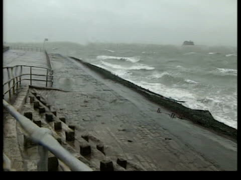 severe weather across the uk; england: hampshire: southsea: ext/raining group of people walking along seafront gv waves crashing beach lms & couple... - road closed sign stock videos & royalty-free footage