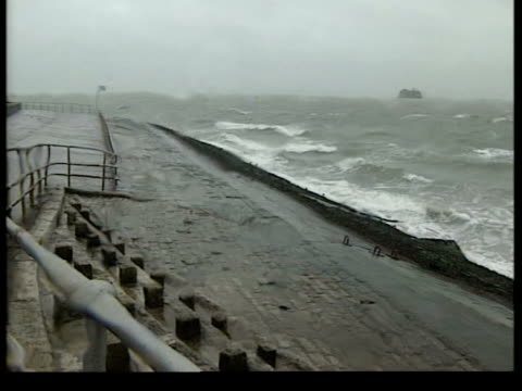 severe weather across the uk; england: hampshire: southsea: ext/raining group of people walking along seafront gv waves crashing beach lms & couple... - road closed englisches verkehrsschild stock-videos und b-roll-filmmaterial