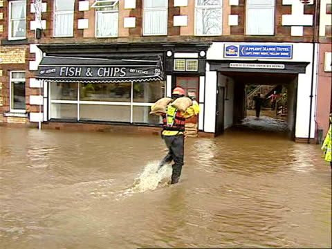 severe weather conditions across uk cumbria man carrying sandbag over shoulder along through flooded area around shops general view of floods around... - sandbag stock videos and b-roll footage