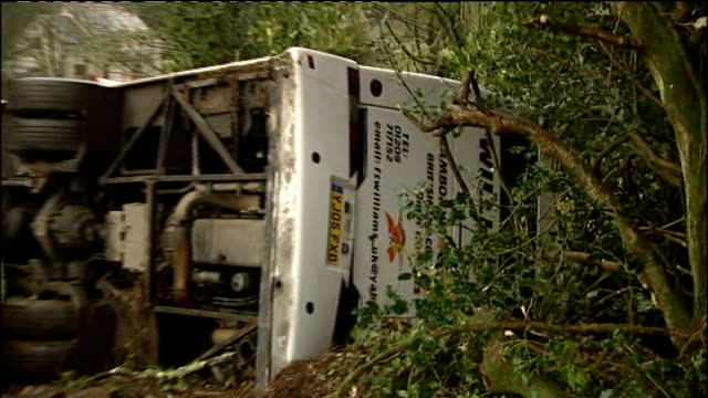 severe weather conditions cause transport accidents; england: cornwall: near penzance: ext various shots of overturned wreckage of coach in ditch at... - ペンザンス点の映像素材/bロール