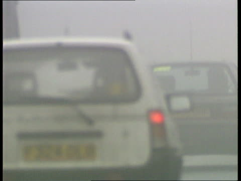 Fog and Ice ITN ENGLAND London Foggy LMS Cars with headlights on towards MS More ditto CBV Wheels of cars away BV Cars only just seen through fog CS...