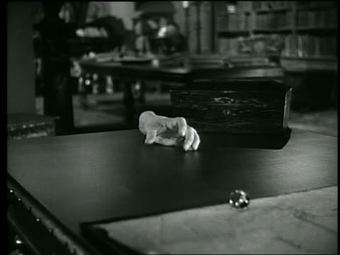 B/W severed hand crawling on table top
