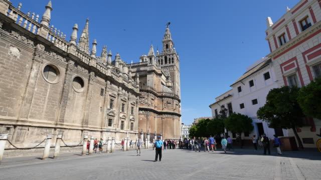 seville cathedral with giralda tower - etwa 12. jahrhundert stock-videos und b-roll-filmmaterial
