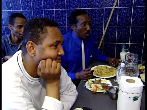 immigration itn england london somalian asylum seeker ahmed korie eating with others in small restaurant ext side ms black man standing in door frame... - ソマリア点の映像素材/bロール