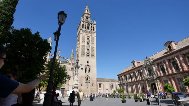 Seville Giralda Tower with street light and tourists