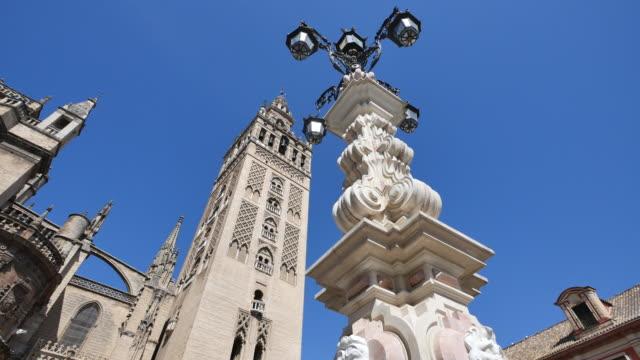 seville lamp post and giralda tower - etwa 12. jahrhundert stock-videos und b-roll-filmmaterial