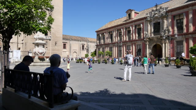 Seville plaza and Archbishops Palace with people on bench