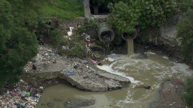 vídeos de stock, filmes e b-roll de sewage draining into polluted water collection pond in mexico city. - sujo