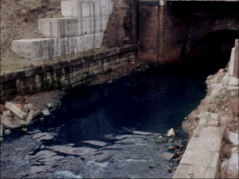 vídeos de stock, filmes e b-roll de sewage systems throughout britain in need of urgent repair general views of polluted river england manchester ext blue dye in river - tintura