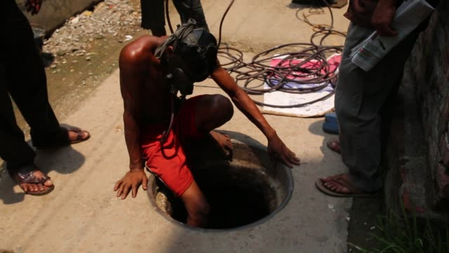 A sewer cleaner of Dhaka City Corporation cleaning out the city's sewers in Dhaka Bangladesh on May 04 2017 Despite a rise in the number of deaths of...
