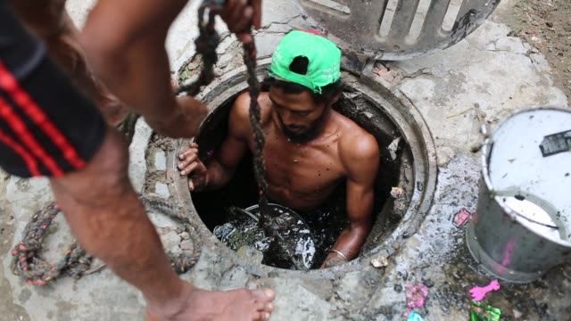 a sewer cleaner of dhaka city corporation cleaning out the city's sewers in dhaka bangladesh on may 04 2017 despite a rise in the number of deaths of... - dhaka stock-videos und b-roll-filmmaterial