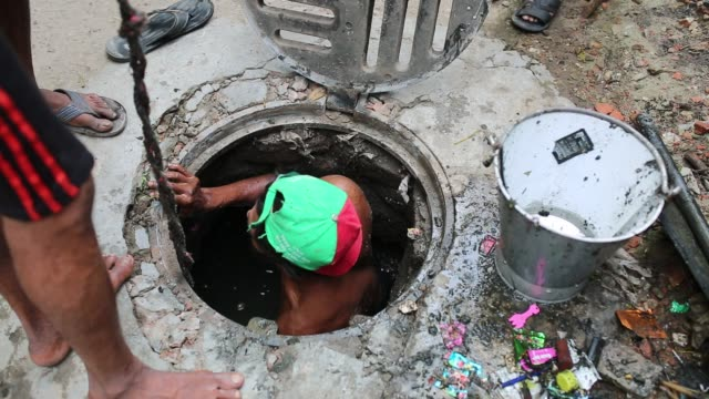 a sewer cleaner of dhaka city corporation cleaning out the city's sewers in dhaka bangladesh on may 04 2017 despite a rise in the number of deaths of... - sewage stock videos and b-roll footage