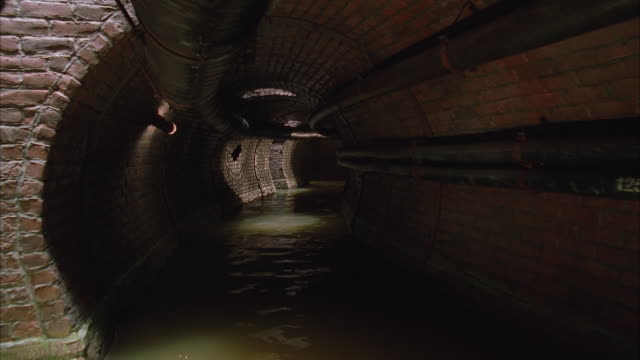 ws pov sewer tunnel with water and brick walls - pipe tube stock videos and b-roll footage