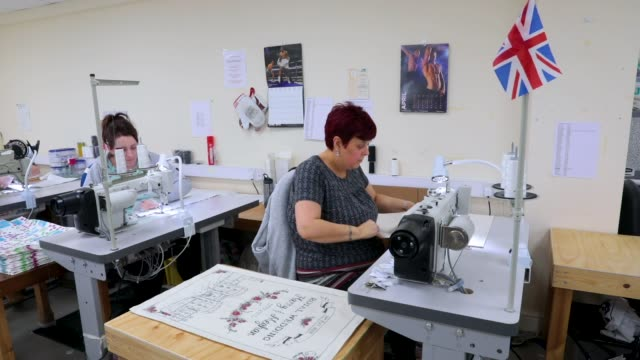 Sewing machinist Tina Clifton sews tea towels by Victoria Eggs to commemorate the wedding of Prince Harry to Meghan Markle at Countryside Art Ltd on...