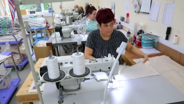 sewing machinist tina clifton sews tea towels by victoria eggs to commemorate the wedding of prince harry to meghan markle at countryside art ltd on... - タオル点の映像素材/bロール