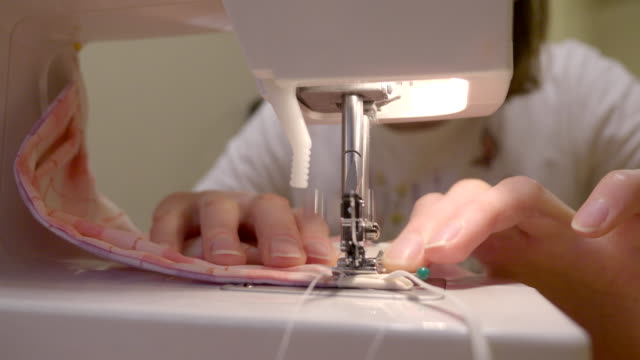sewing medical masks for hospitals at coronavirus pandemic time. - a helping hand stock videos & royalty-free footage