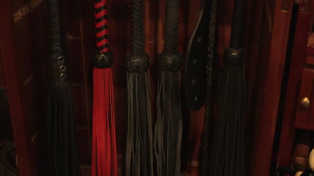 vídeos de stock, filmes e b-roll de sex whips in bedroom closet on display, close-up - roupa de fetiche