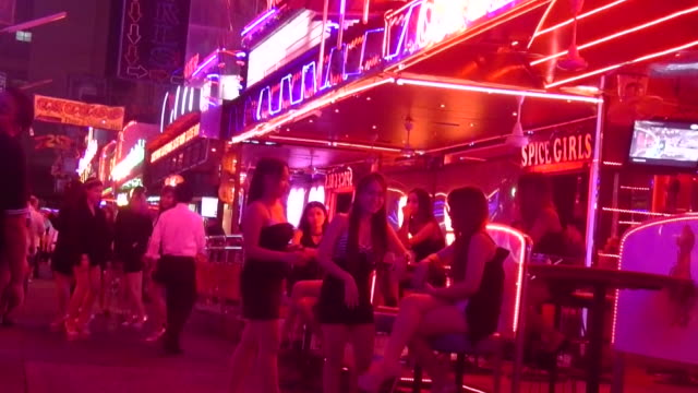Sex workers wait for customers under the neon lights on Soi Cowboy Bangkok on the day the government relaxed mourning restrictions The King of...