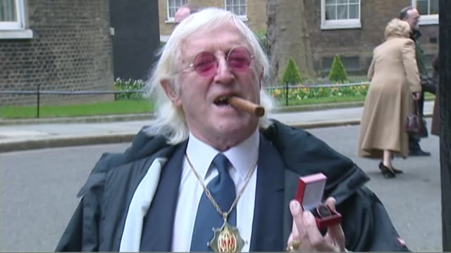 sexual abuse victims asked to share their experiences for research lib downing street ext jimmy savile posing with bevan boys badge - ジミー サヴィル点の映像素材/bロール