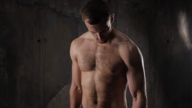 vídeos de stock e filmes b-roll de sexy bare-chested male athlete with dumbbells pumping up biceps - musculado