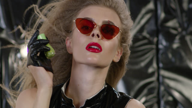 sexy blond fashion model in latex dress, black leather gloves and sunglasses licks green nail polish bottle. fashion video. - latex stock videos & royalty-free footage