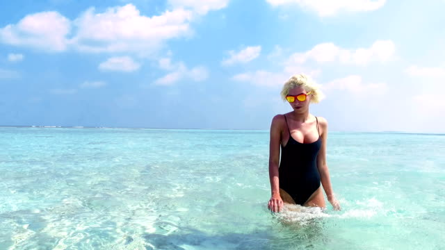 Sexy blonde woman walking through shallow water on Maldives