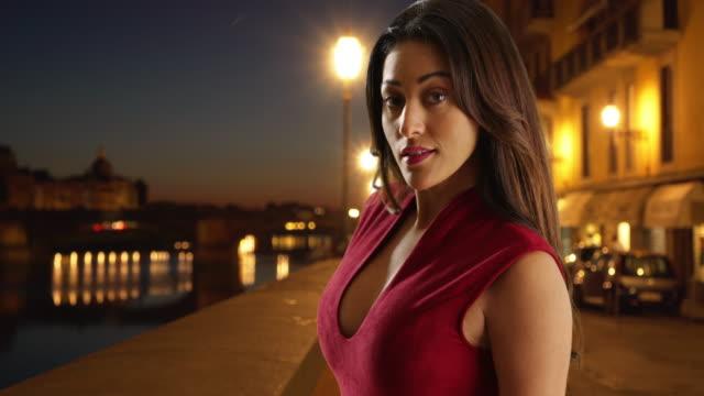 sexy confident young latina woman on a florence street at night - 赤のドレス点の映像素材/bロール