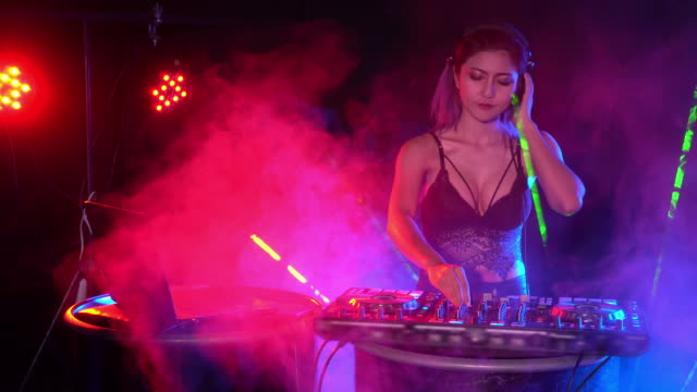 Sexy DJ playing music, mixing tracks on a mixer in a nightclub.