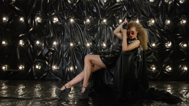 sexy fashion model dressed in black latex mini dress, relaxing in armchair. fashion video. - latex stock videos & royalty-free footage