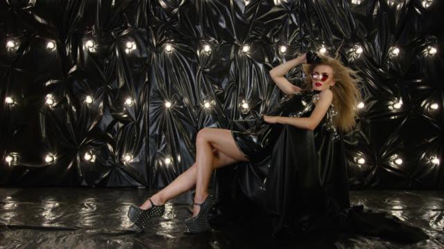 sexy fashion model dressed in black latex mini dress, relaxing in armchair. fashion video. - haute couture stock videos and b-roll footage