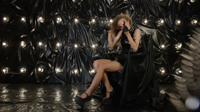sexy fashion model in latex mini dress and sunglasses sits in armchair and holds light bulb and lipstick. fashion video. - lip liner stock videos & royalty-free footage