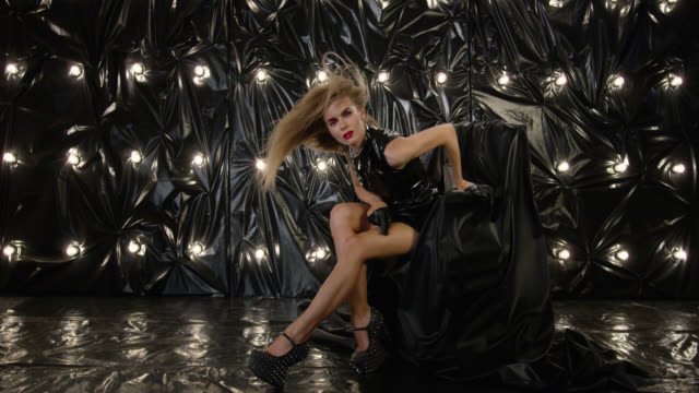 sexy fashion model in latex mini dress sits in armchair and holds red lipstick, playing with it. fashion video. - dress stock videos & royalty-free footage