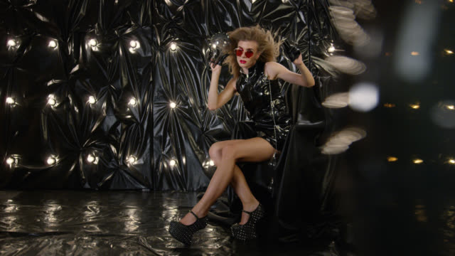 sexy fashion model in latex mini dress sits in armchair and holds red lipstick, playing with it. fashion video. - haute couture stock videos and b-roll footage