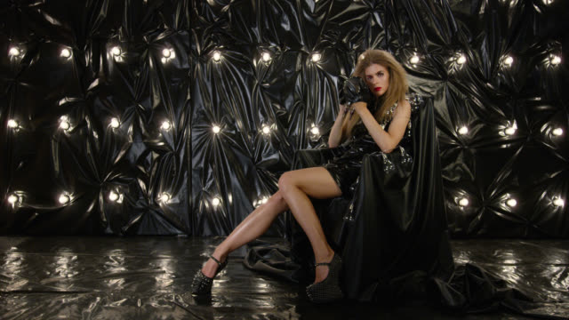 sexy fashion model in latex mini dress sits in armchair and holds light bulb, playing with it. fashion video. - lip liner stock videos & royalty-free footage