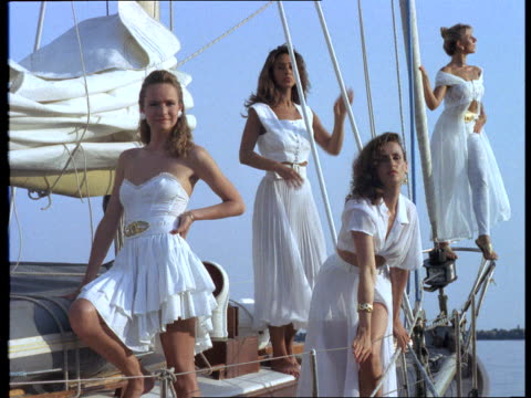Sexy models wearing white dresses pose on a sailboat.