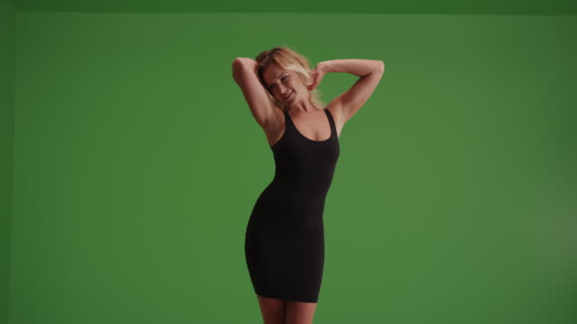 sexy woman dancing in little black dress on green screen. - turning stock videos & royalty-free footage