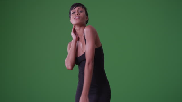 vidéos et rushes de sexy woman in tight black dress dancing on grey background on green screen - projection screen