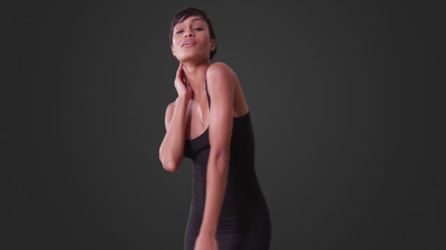 sexy woman in tight black dress dancing on grey background - black dress stock videos & royalty-free footage