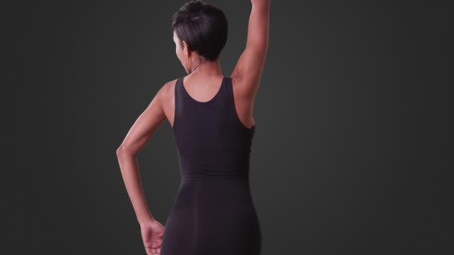 sexy woman in tight black dress dancing on grey background - dress stock videos and b-roll footage