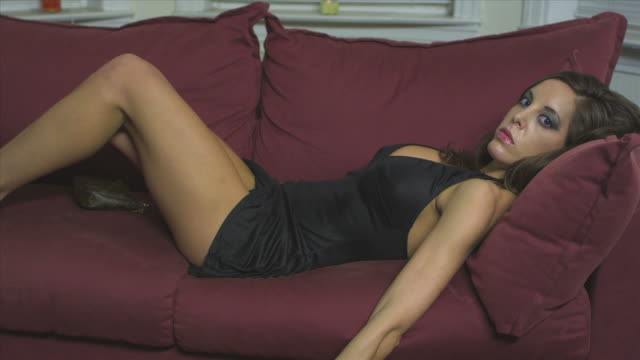 HD CRANE: Sexy woman laying on sofa