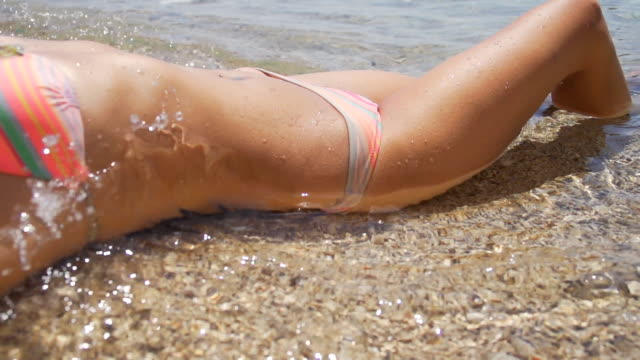 hd super slow mo: sexy woman lying on the beach - sunbathing stock videos and b-roll footage