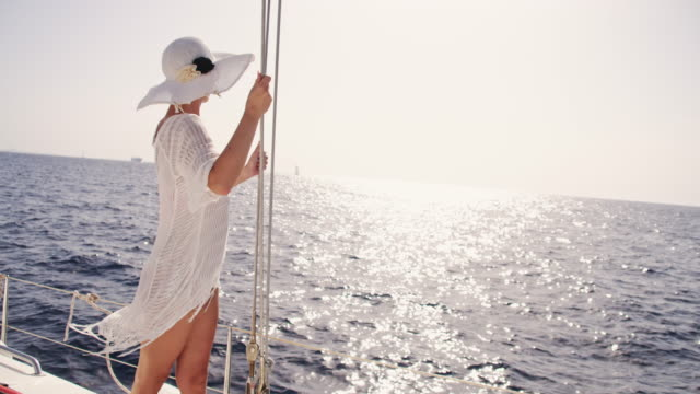 slo mo sexy woman on the bow of a sailboat - sun hat stock videos & royalty-free footage