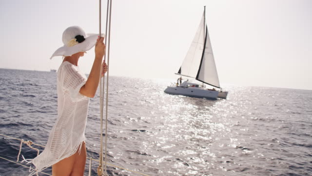 SLO MO Sexy woman on the bow of a sailboat